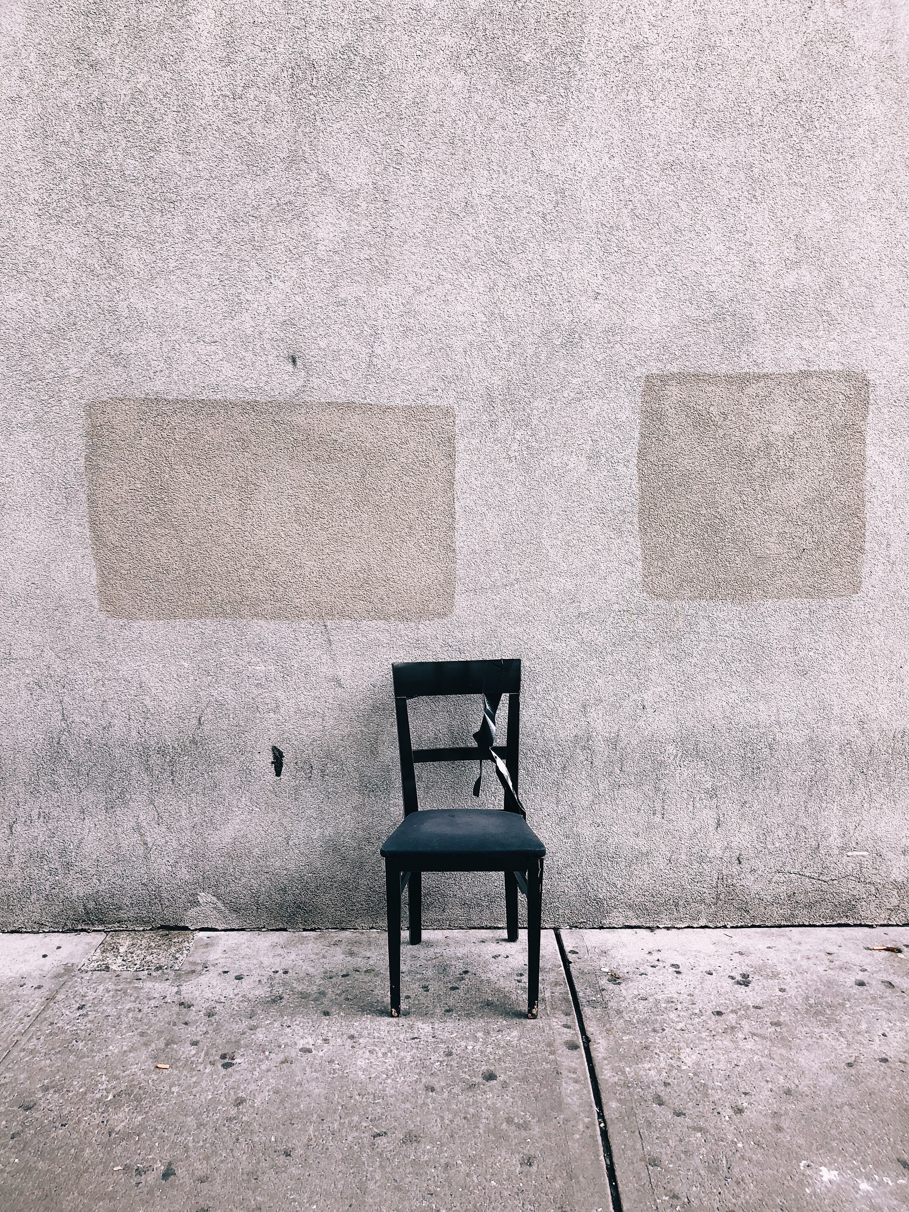 black dining chair beside wall