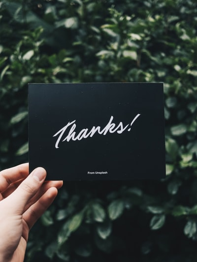 person holding Thanks card