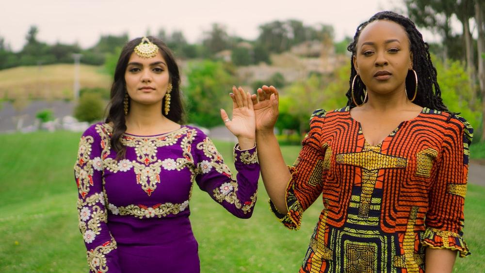 two women standing on field