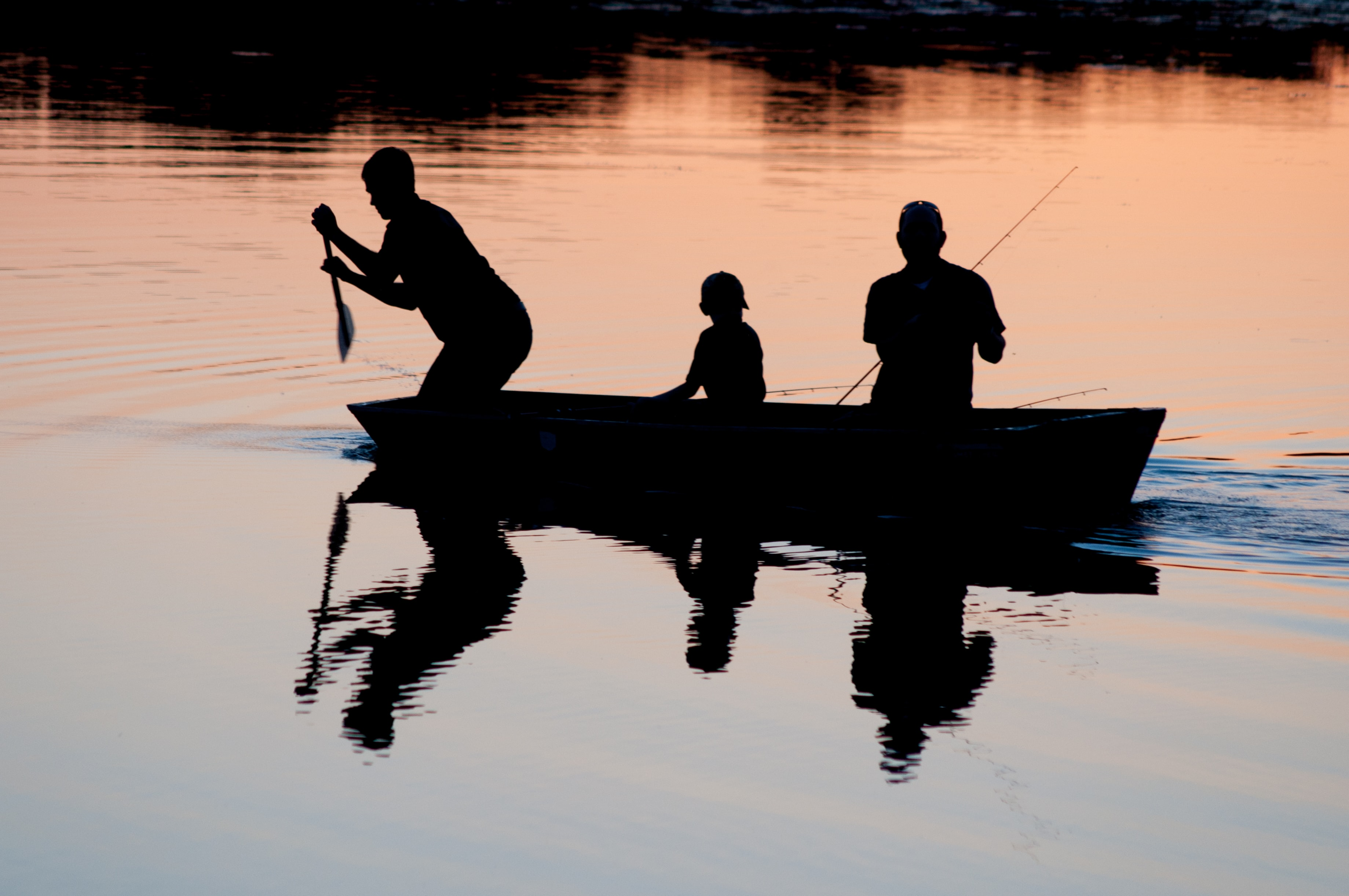 silhouette of three person riding on boat on body of water