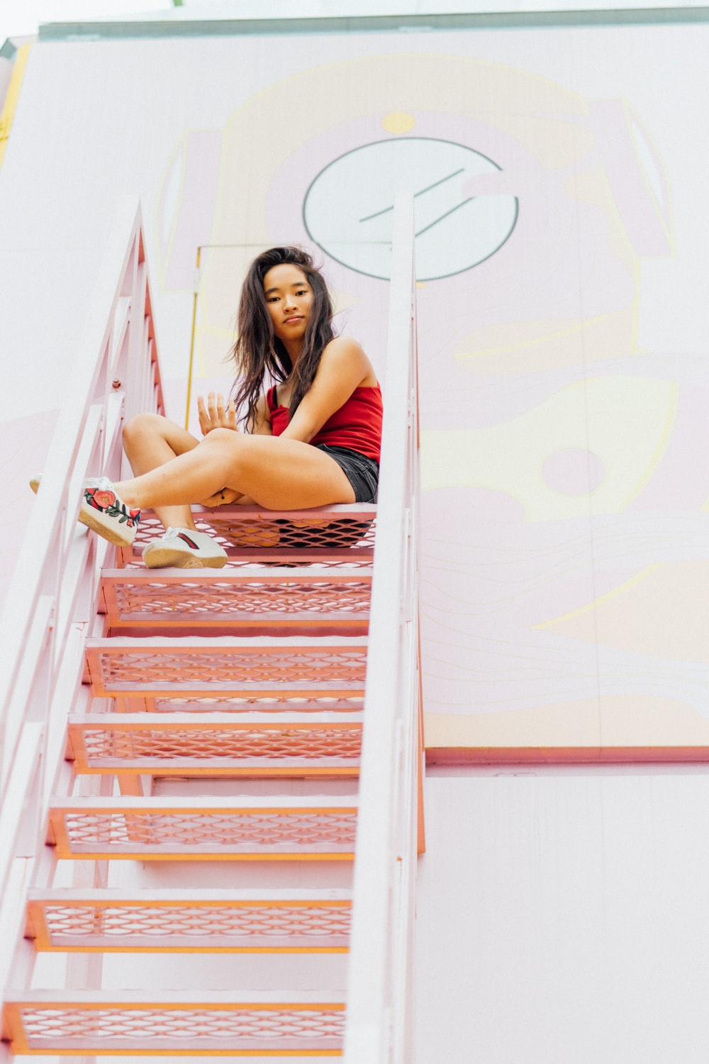 woman sitting on red gray metal stair