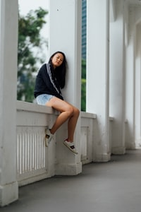 woman sitting on handrail