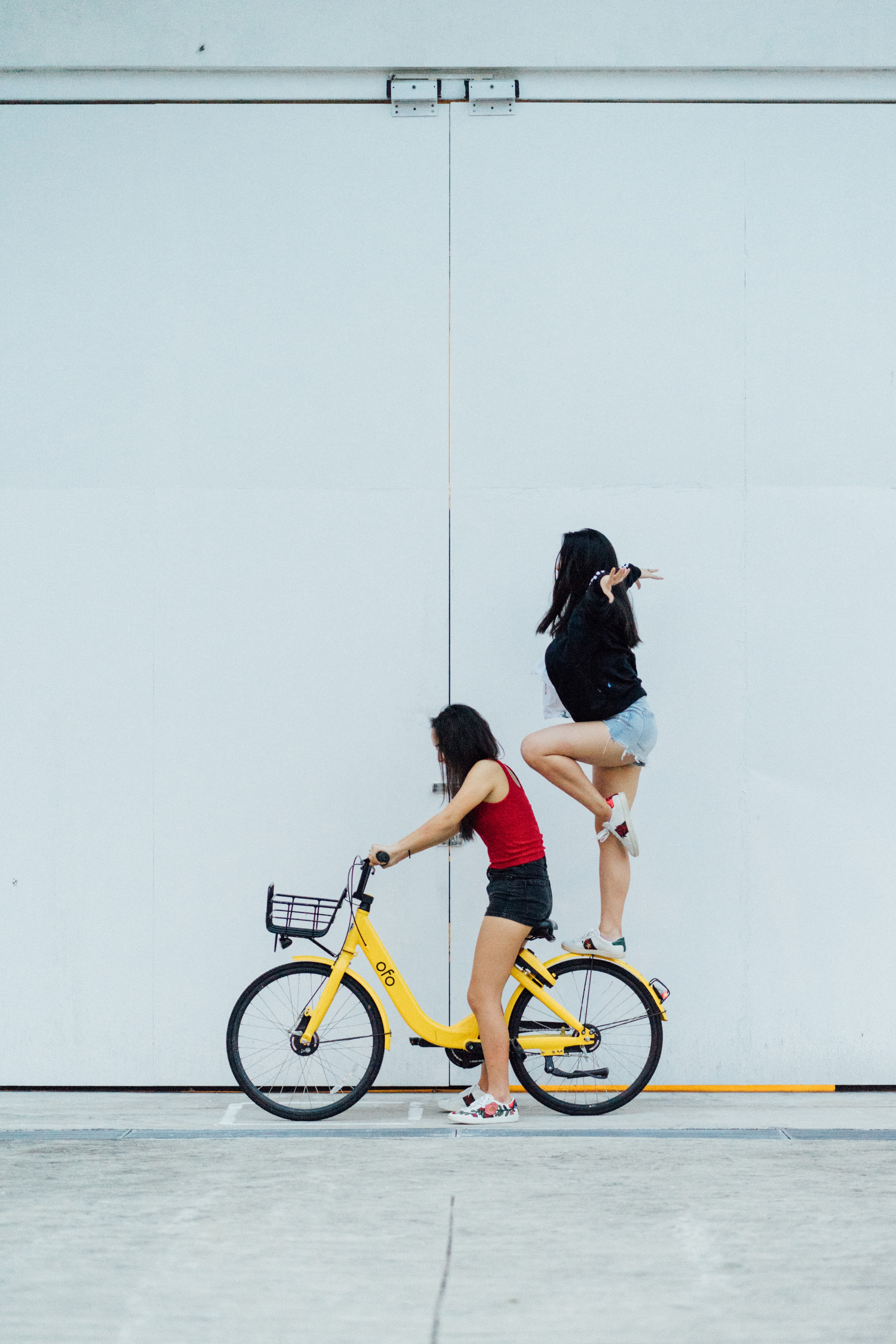 woman riding bicycle with another woman standing on rear fender near wall