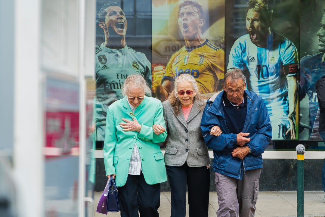 3 Elderly people walking with pictures of famous players behind them