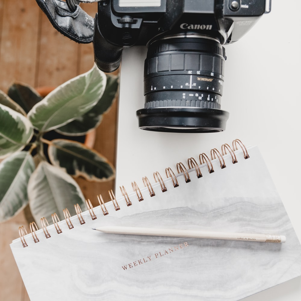 black Canon DSLR camera on table beside notebook
