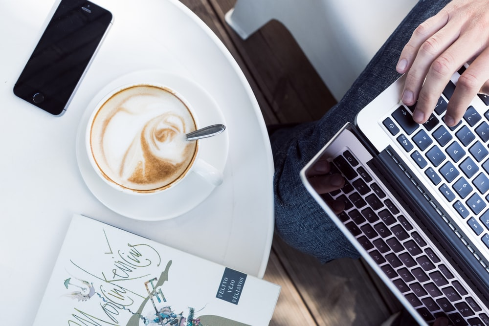 person using laptop near cup of coffee