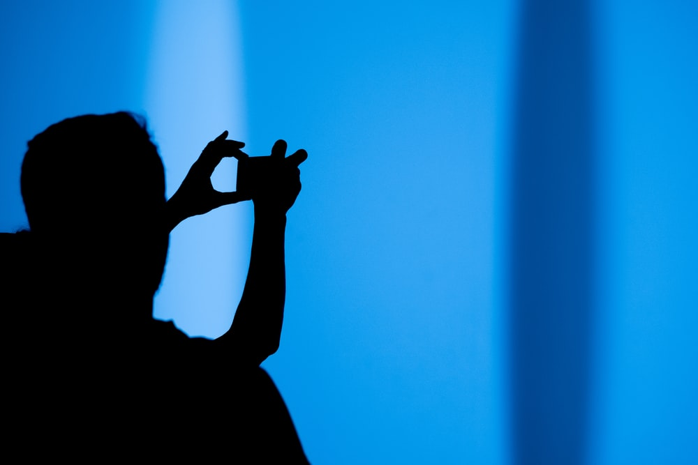 silhouette of a person using a gadget