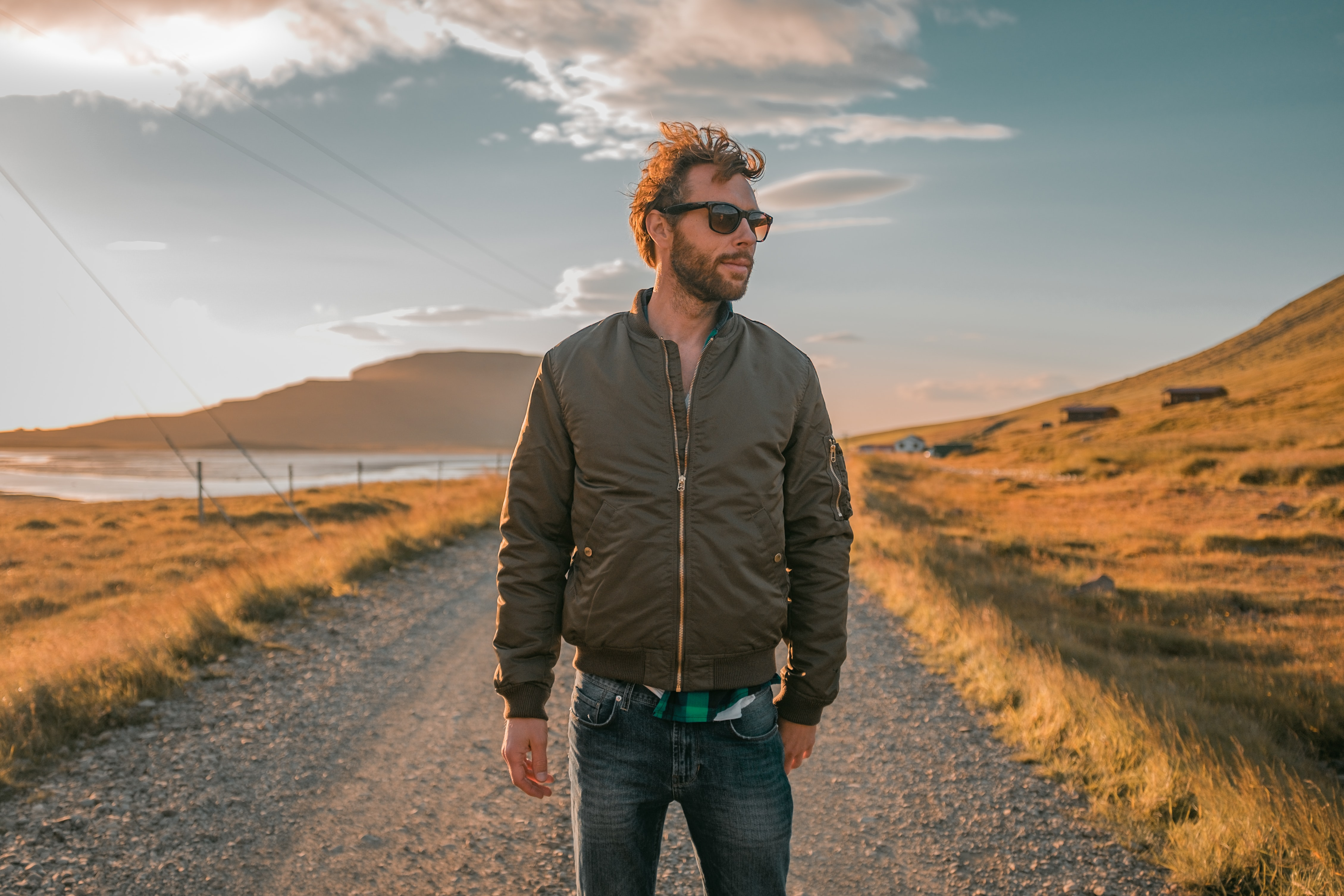 man wearing bomber jacket standing in front of pathway