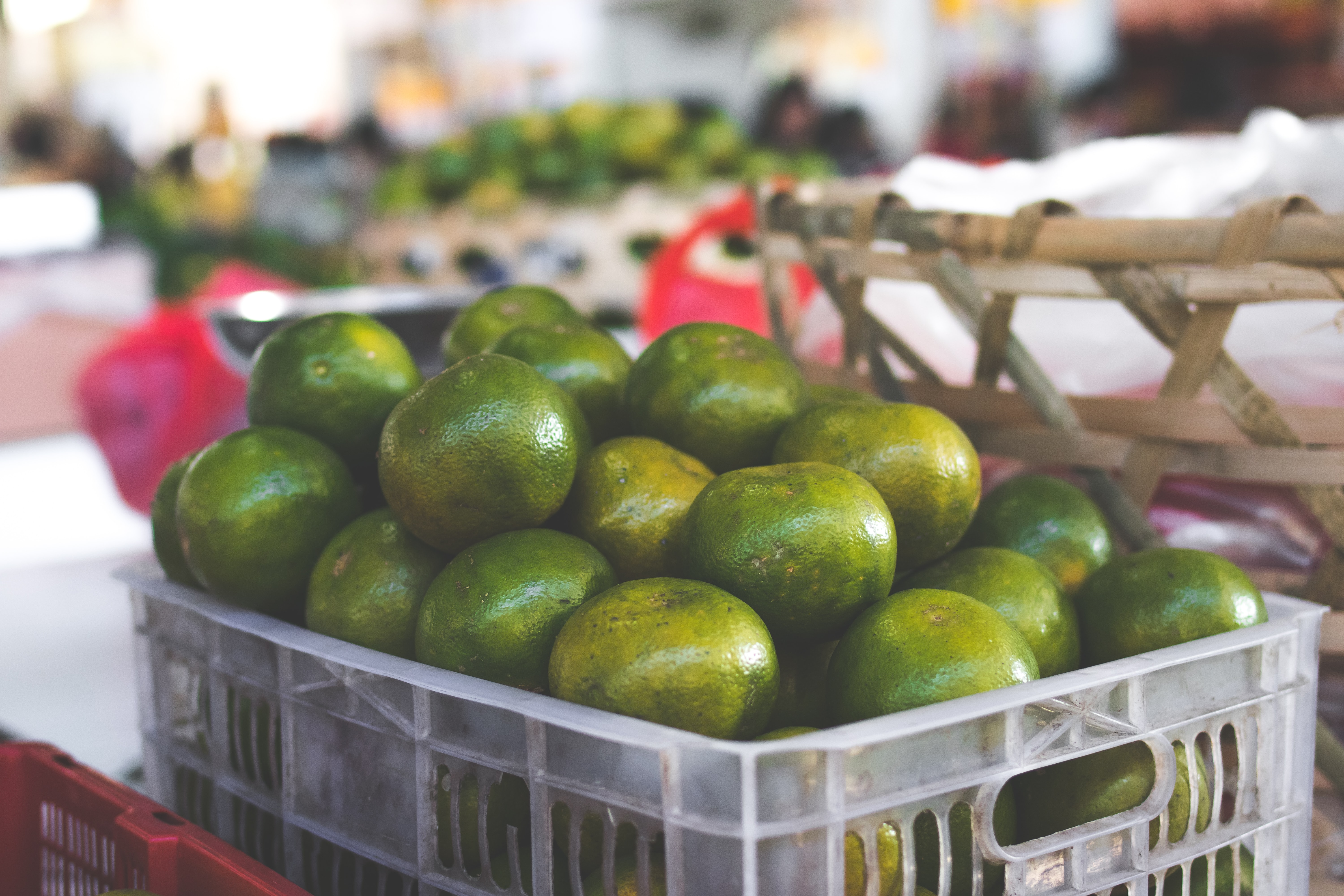 green citrus fruits in white crate