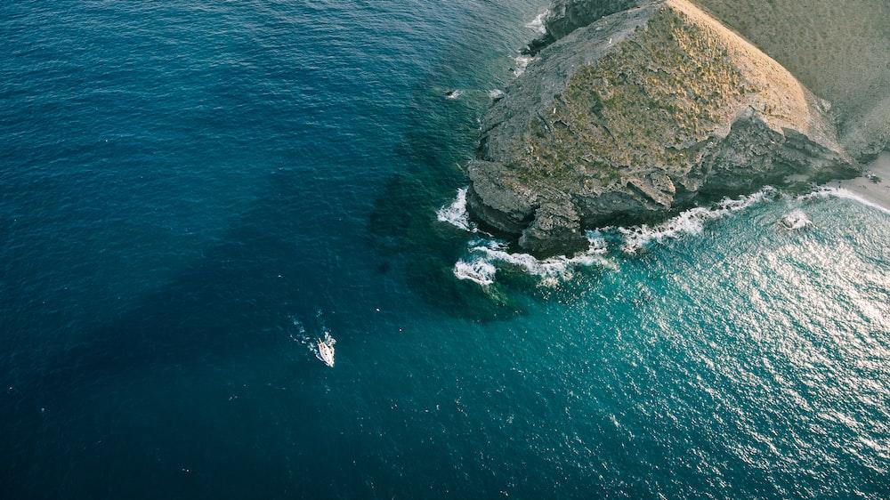 aerial photo of boat sailing on sea near rock mountain