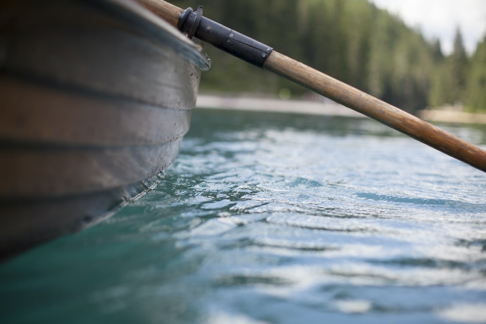 brown row boat on the body of water in closeup photography