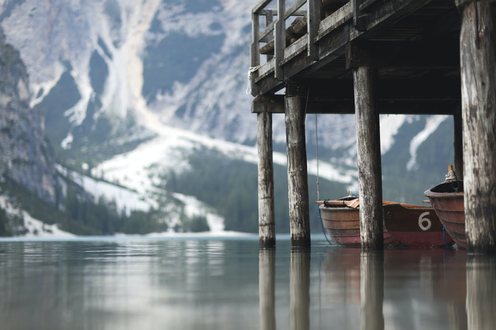 two brown wooden canoe under dock with mountain in distance