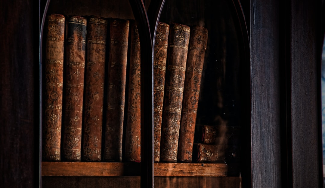 Leather bound books sits quietly waiting for a reader. Antique books in a bookcase. Toronto, Ontario
