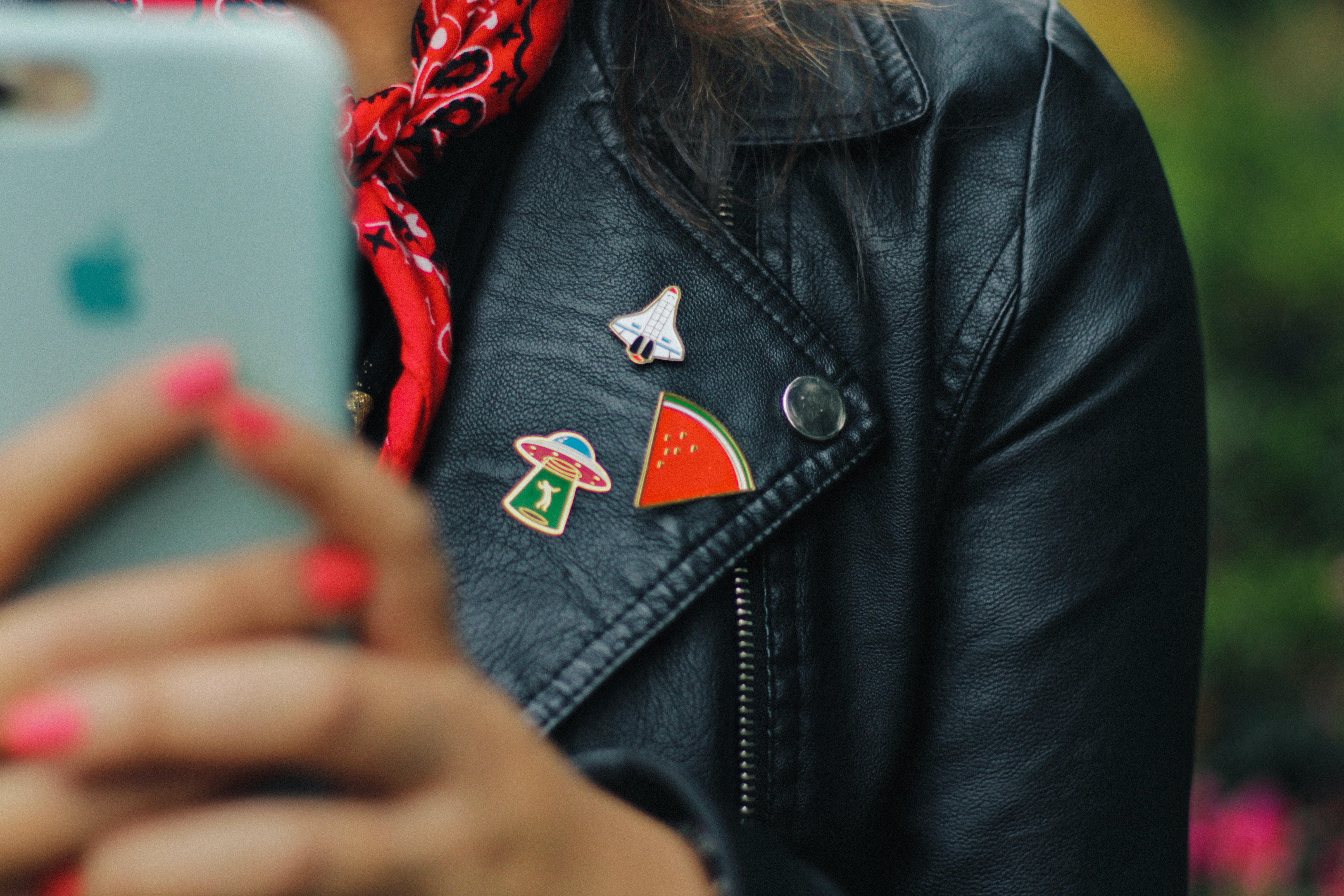 person wearing black leather jacket holding mobile phone