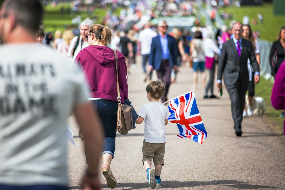 selective focus photography of boy holding U.K. flag walking on pathway full of people