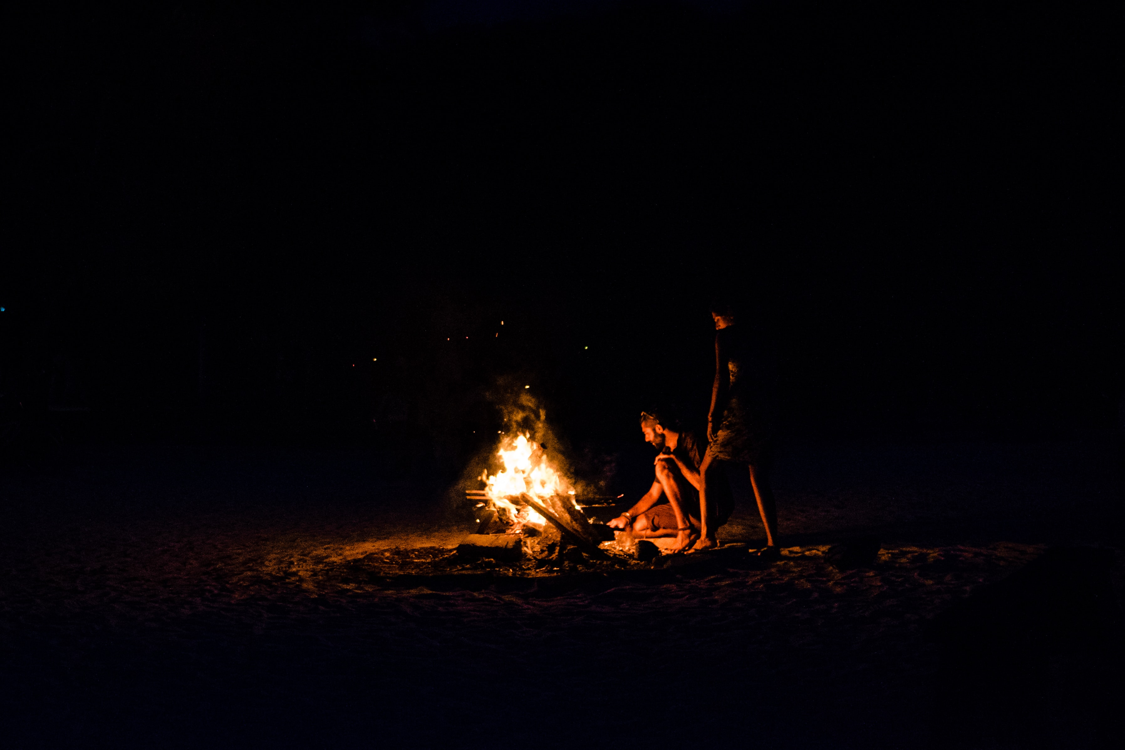 three person sitting near bornfire