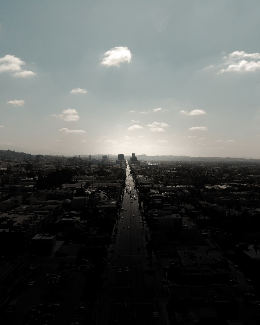 grayscale photography of city with high-rise buildings viewing road