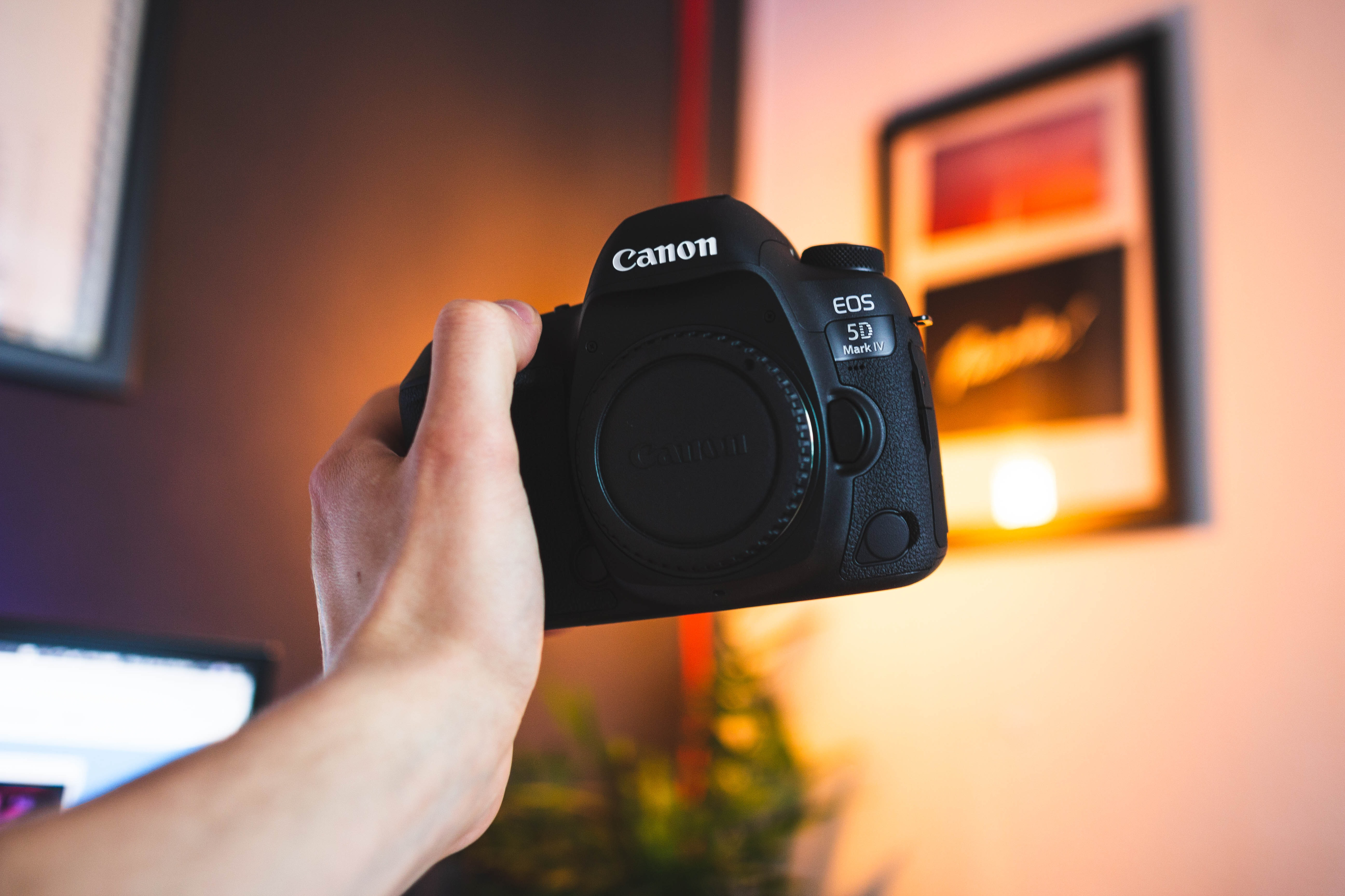 person holding black Canon EOS 5D inside room