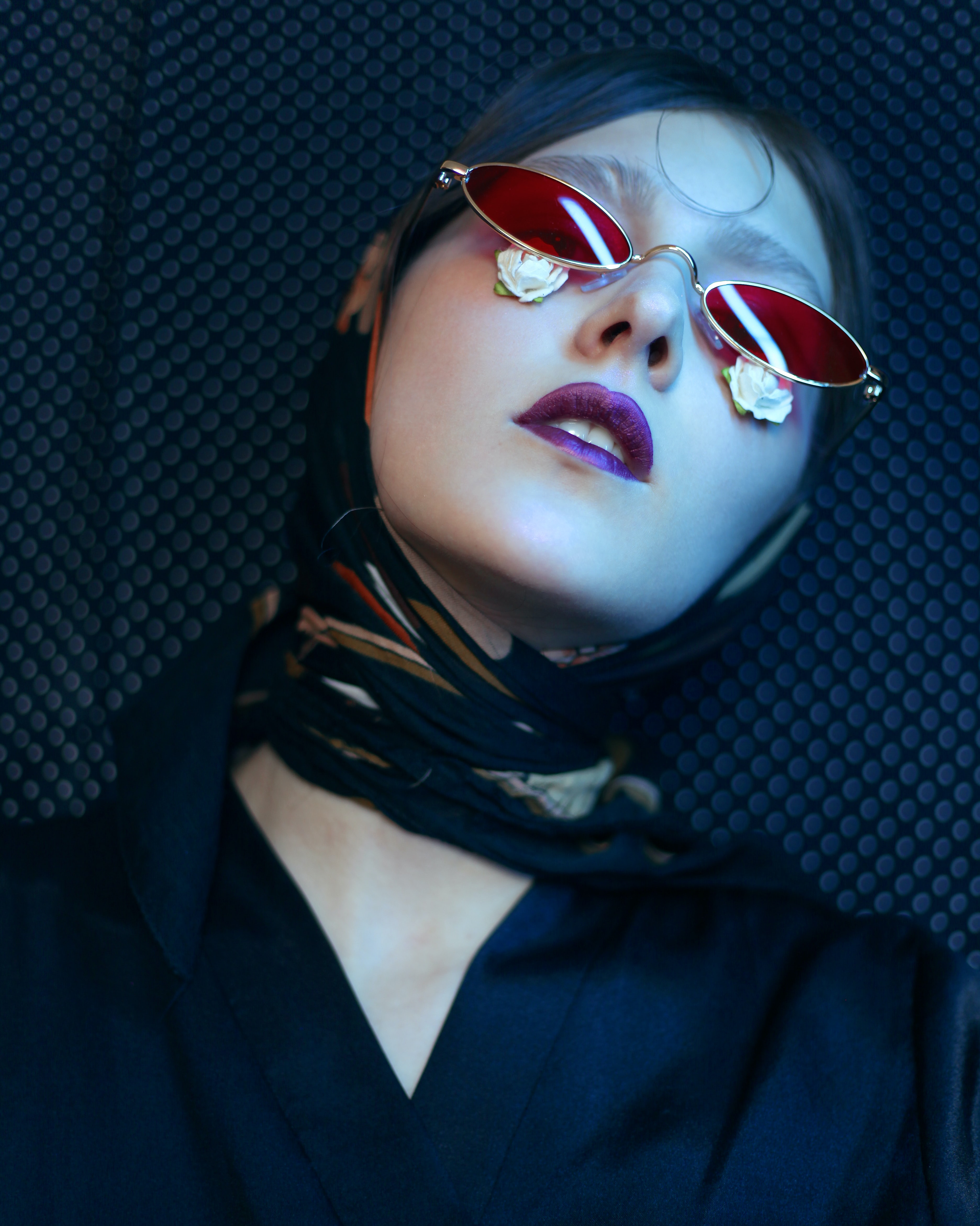 woman wearing gold framed red lens eyeglasses and leaning on gray and black wall