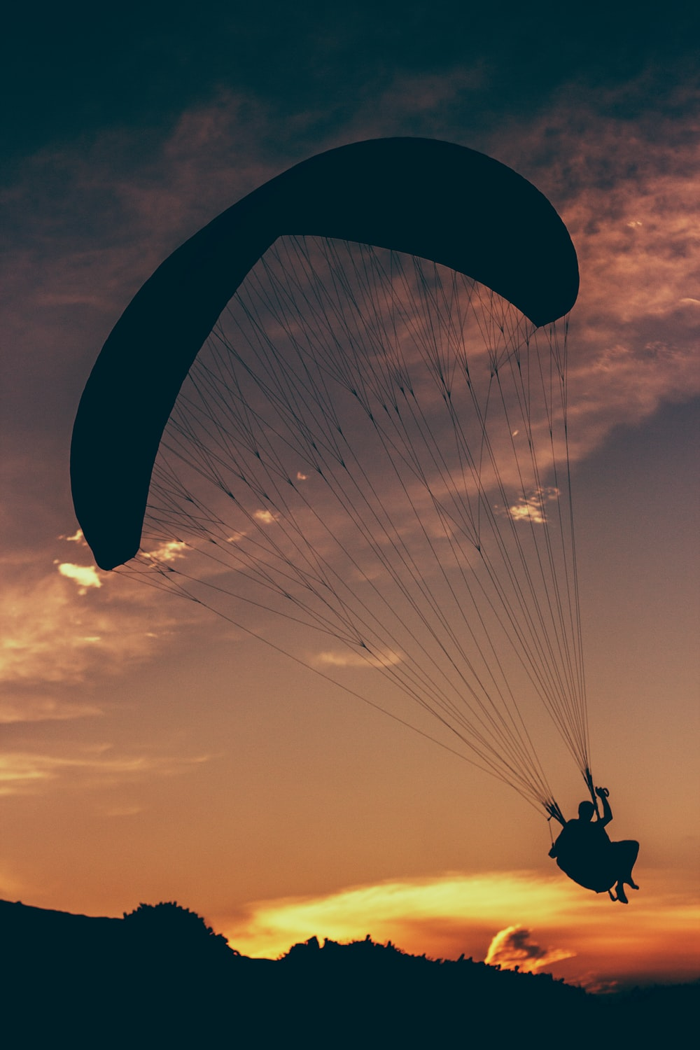 silhouette of man in parachute at golden hour