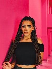 woman in black off-shoulder top standing near pink wall