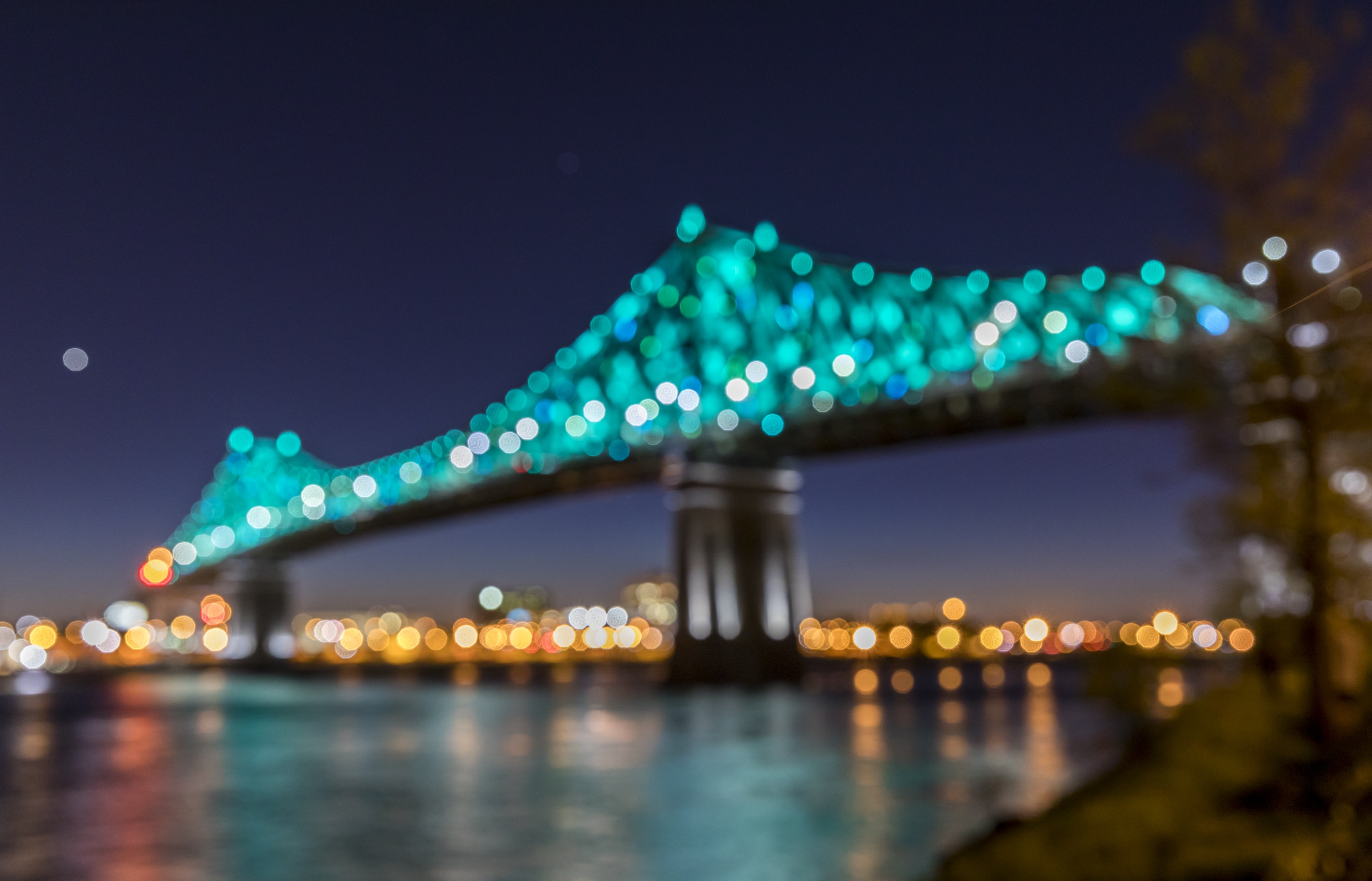 suspension bridge with teal lights during nighttime