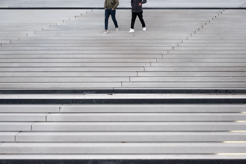 two persons walking through stairs
