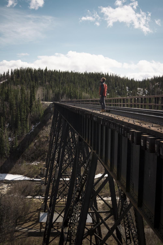 man looking up standing on bridge during daytime