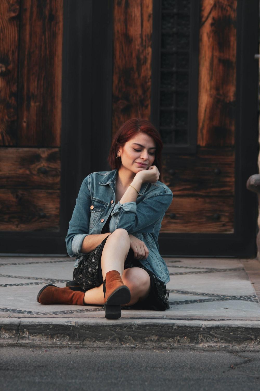 woman wearing blue denim jacet sitting on pavement