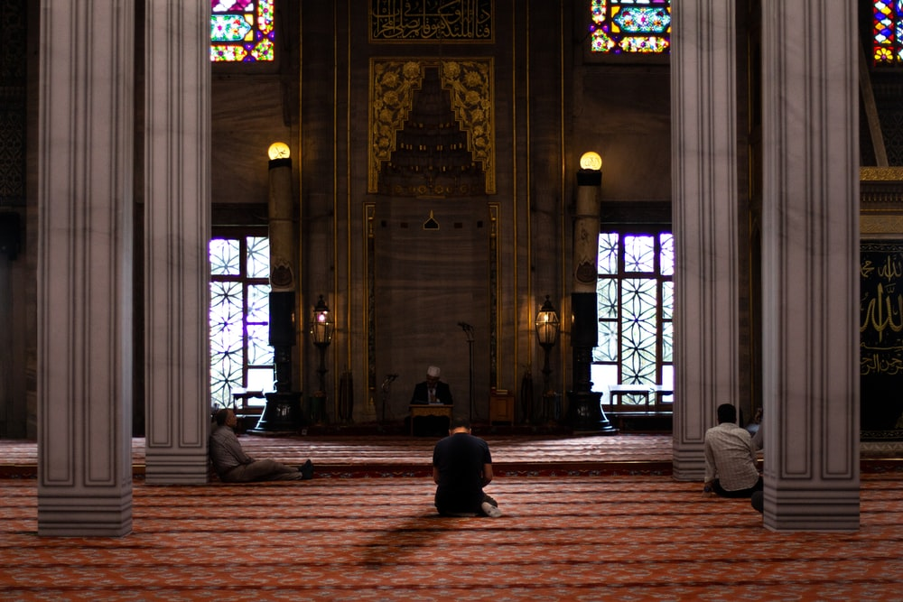 three men sitting inside mosque