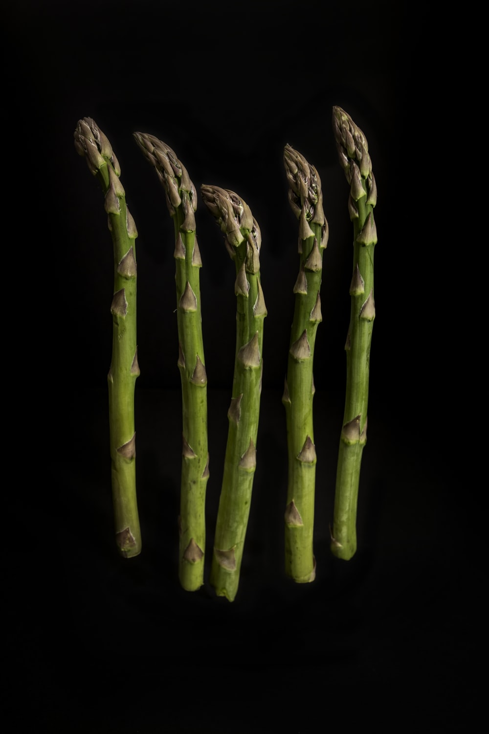 six green-and-brown asparagus with black background