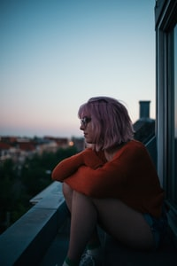 woman sitting near window near building