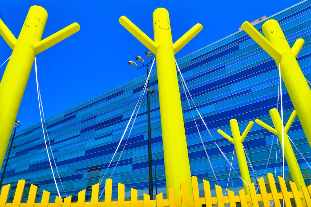 three yellow poles in back of yellow fence
