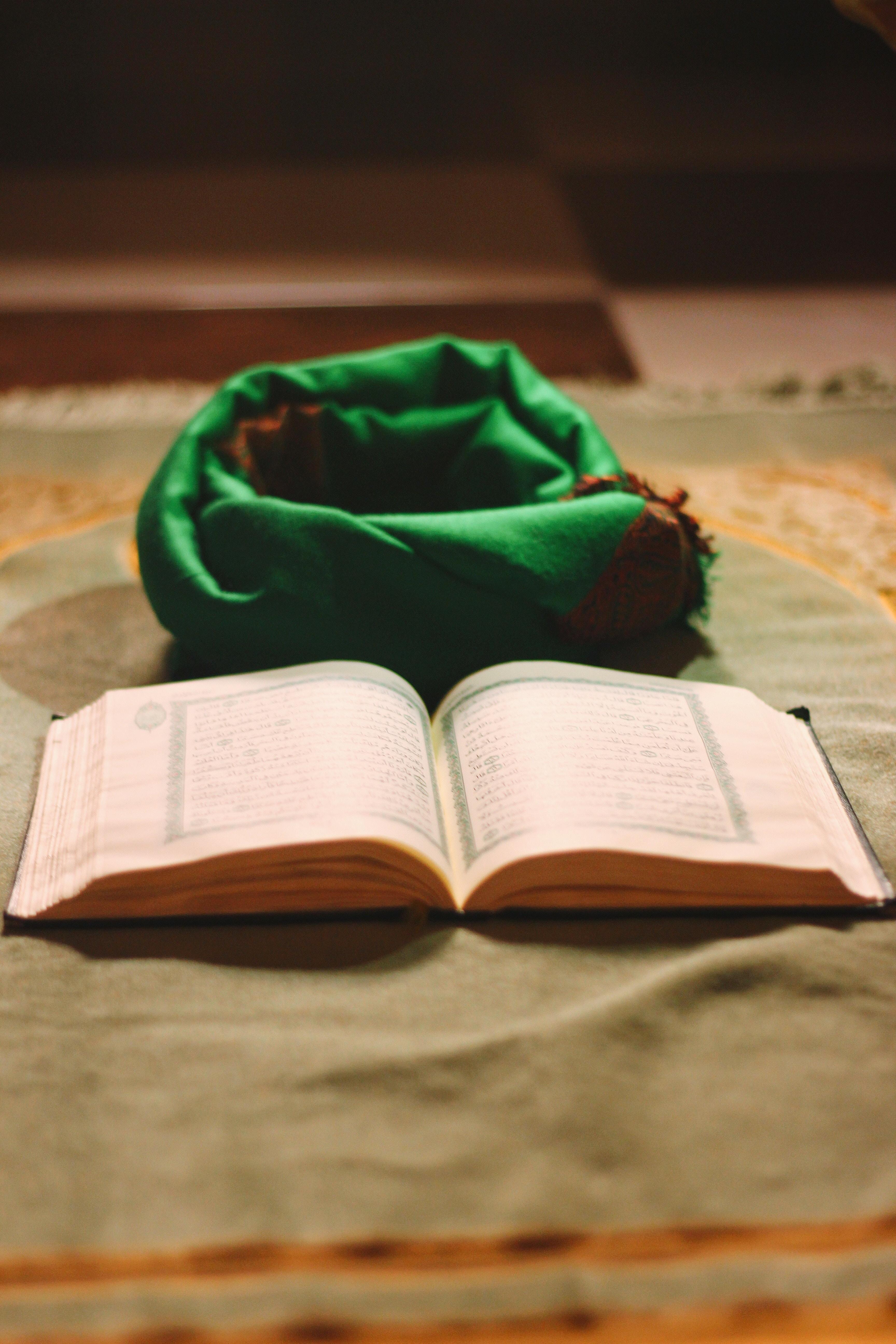 white book beside green textile