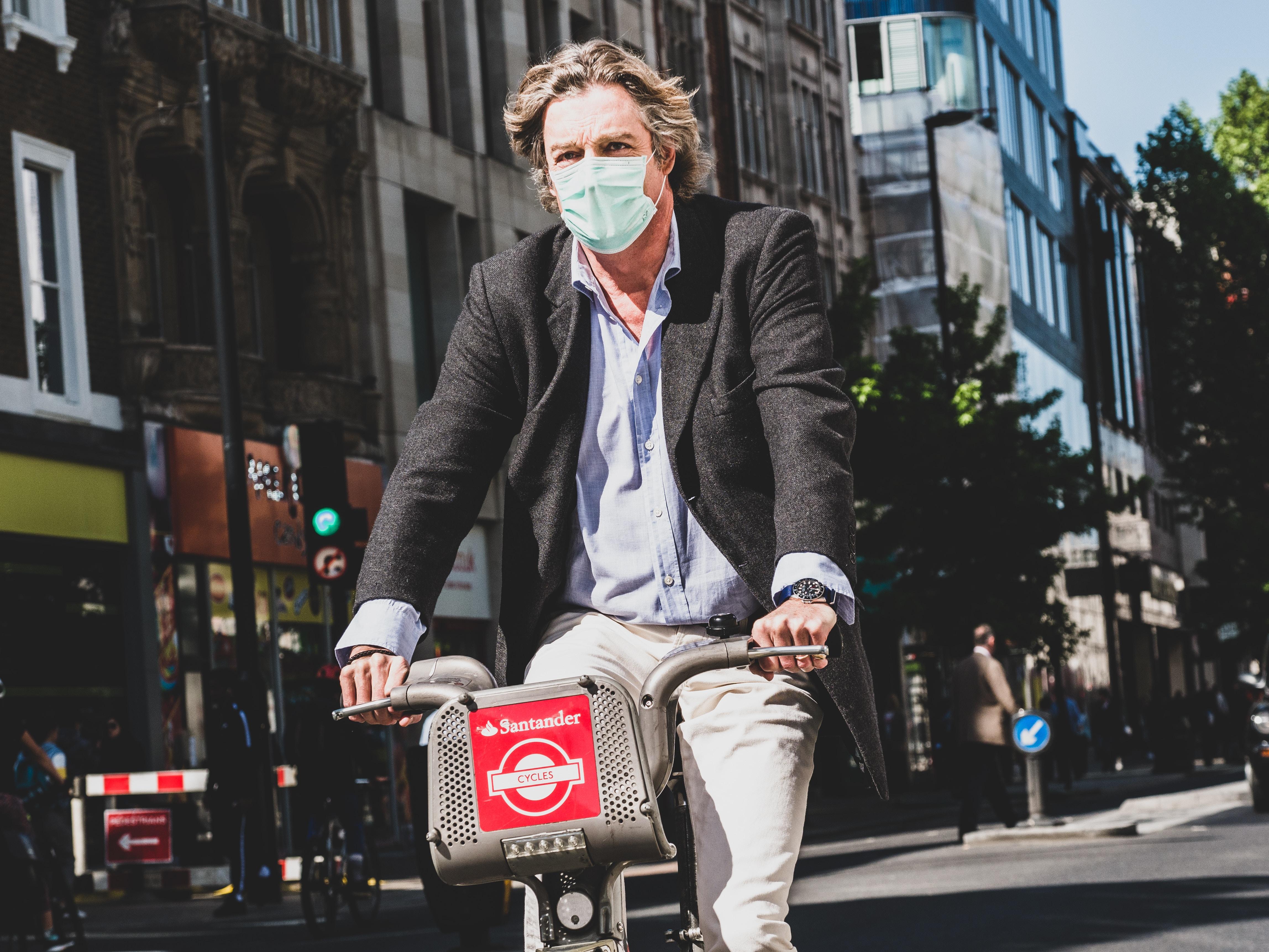 man wearing mask riding bicycle
