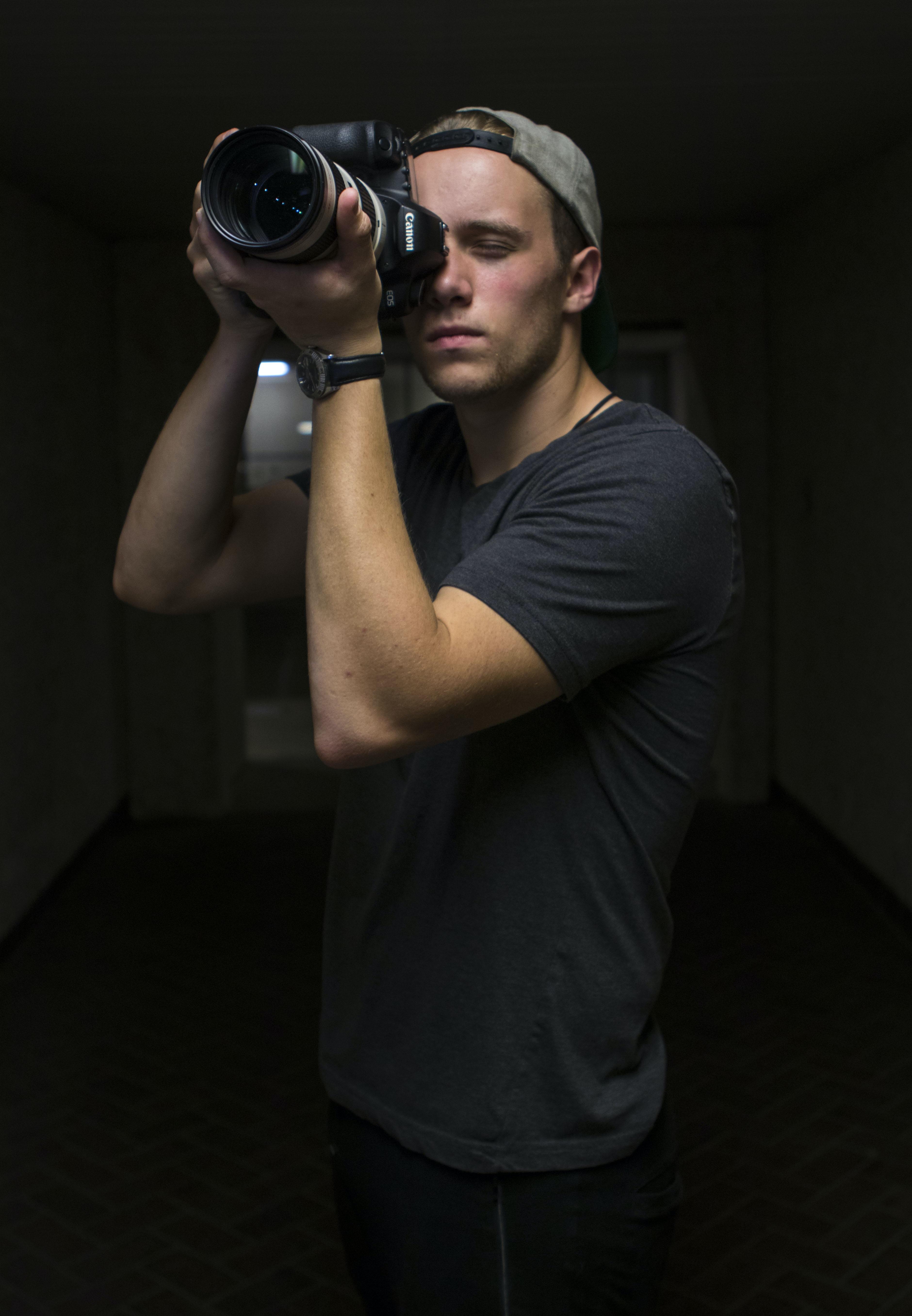 man taking photo using Canon DSLR camera