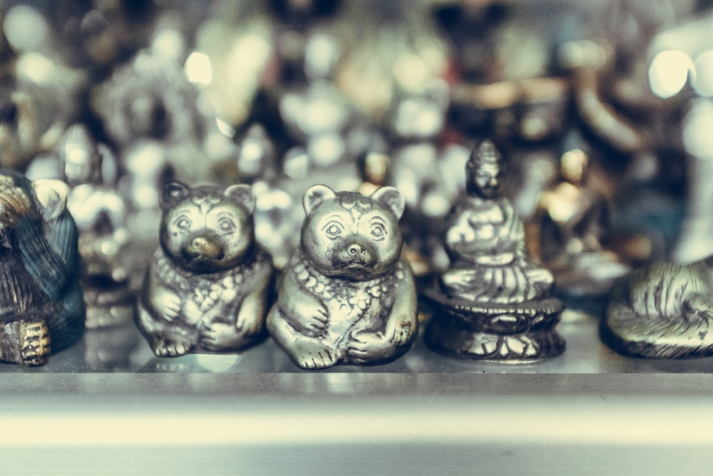 close-up photography of silver-colored bear and Buddha figurines