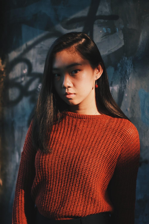 woman in red sweater posing near gray wall