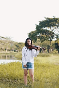 woman standing holding violin near river