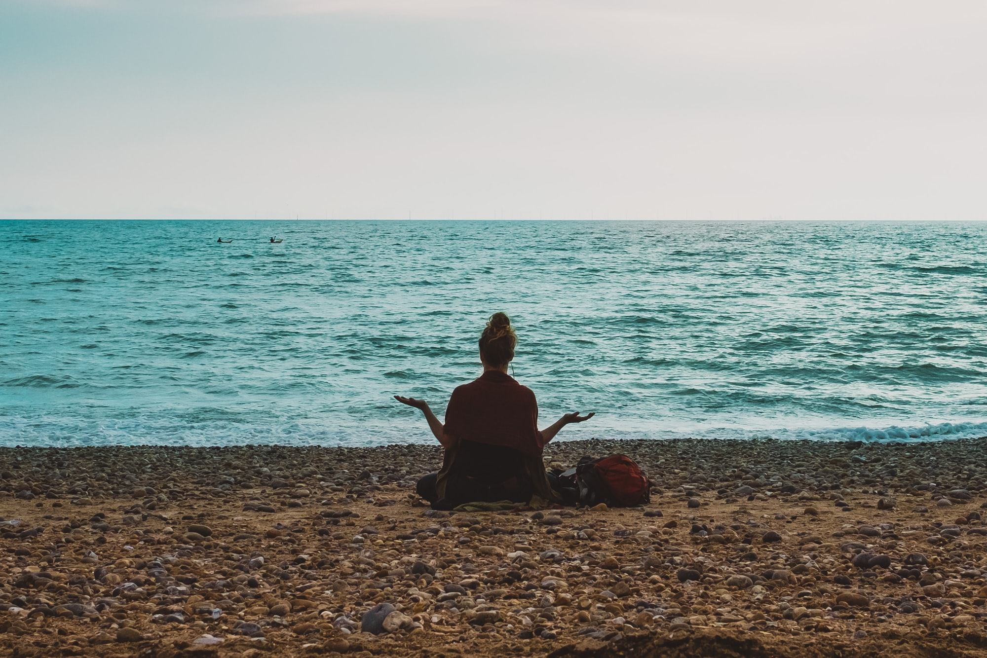 Brunette meditating on Brighton Beach, UK with arms outstretched