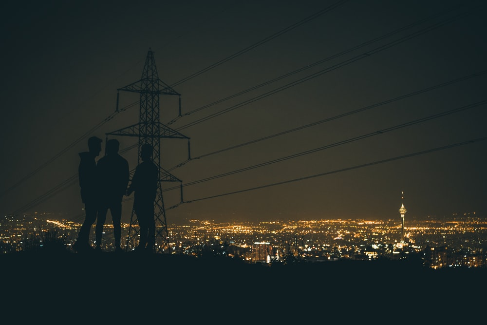 silhouette of 3 people standing near crane