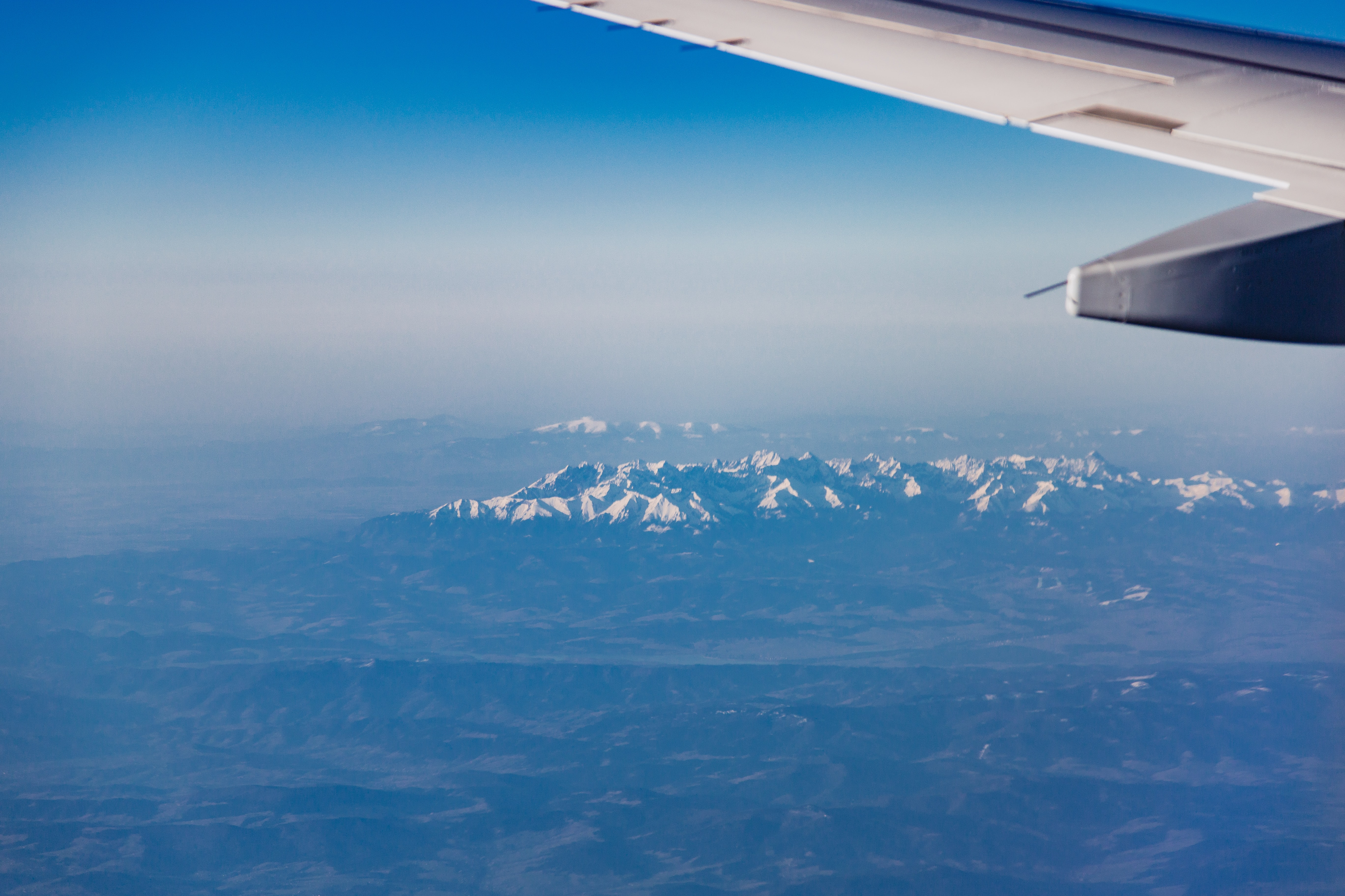 white airplane wing above a snow mountains