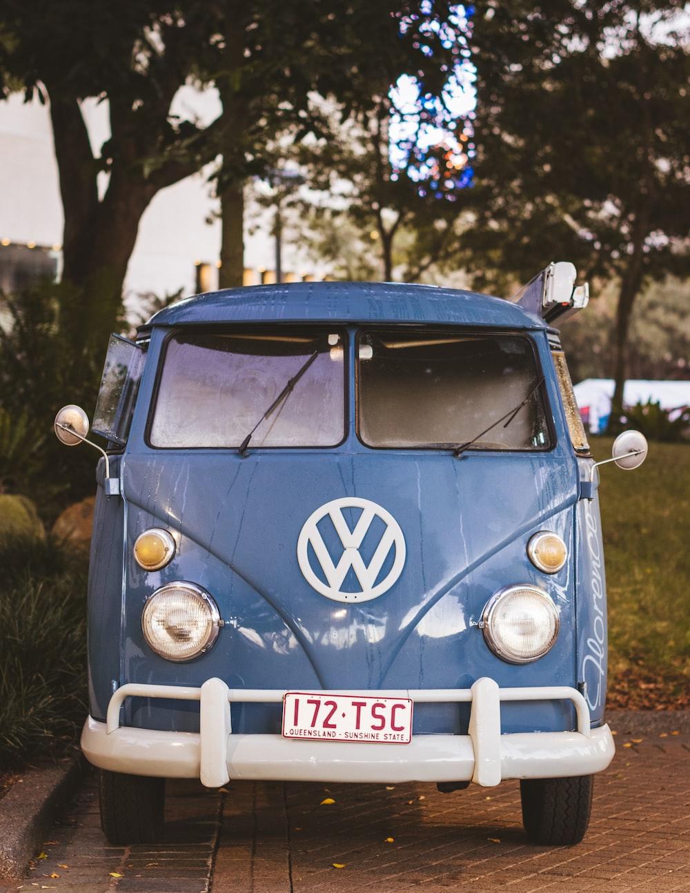 classic blue Volkswagen minivan parked under tree at daytime