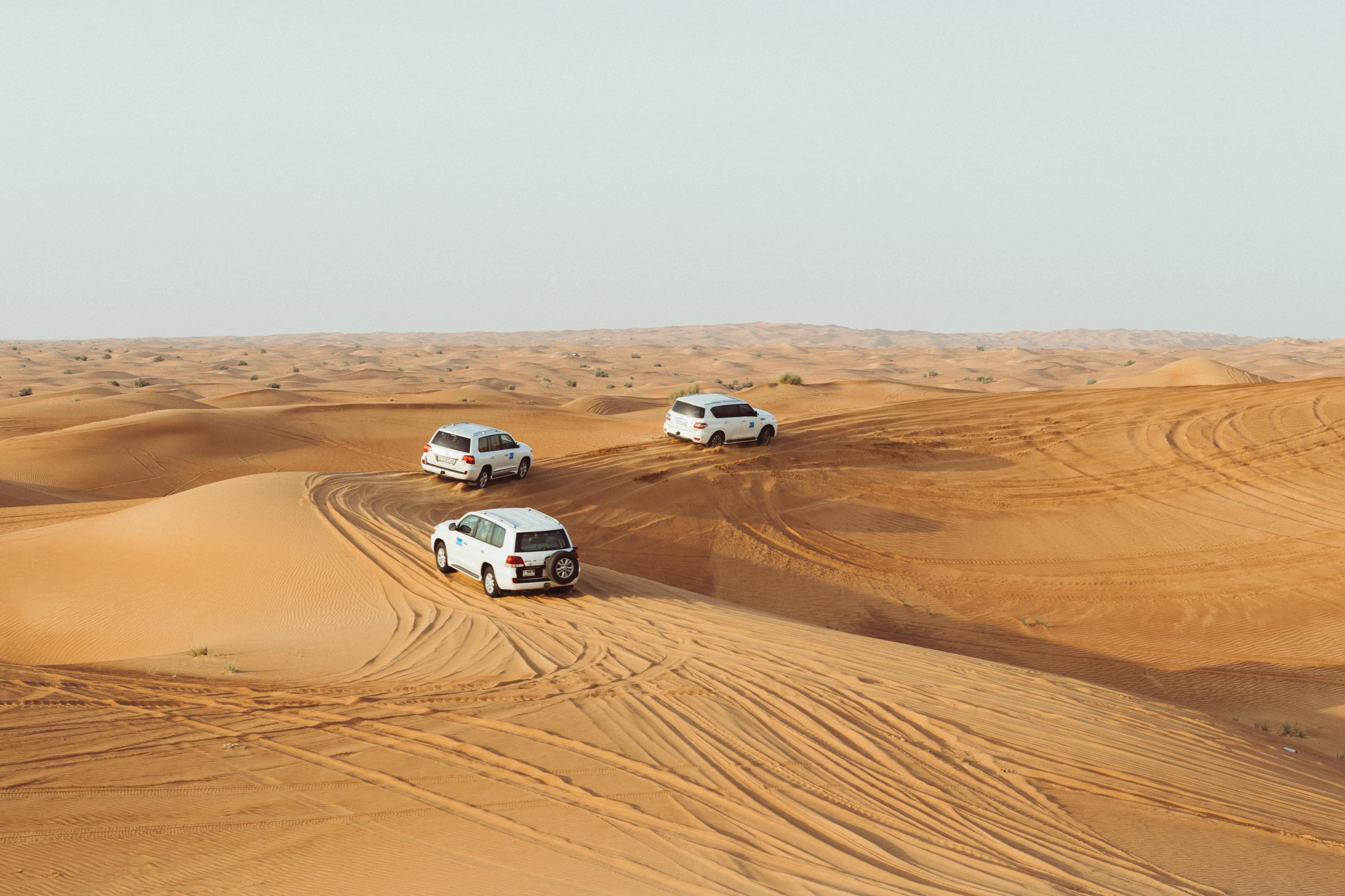three white vehicles moving in desert under gray sky