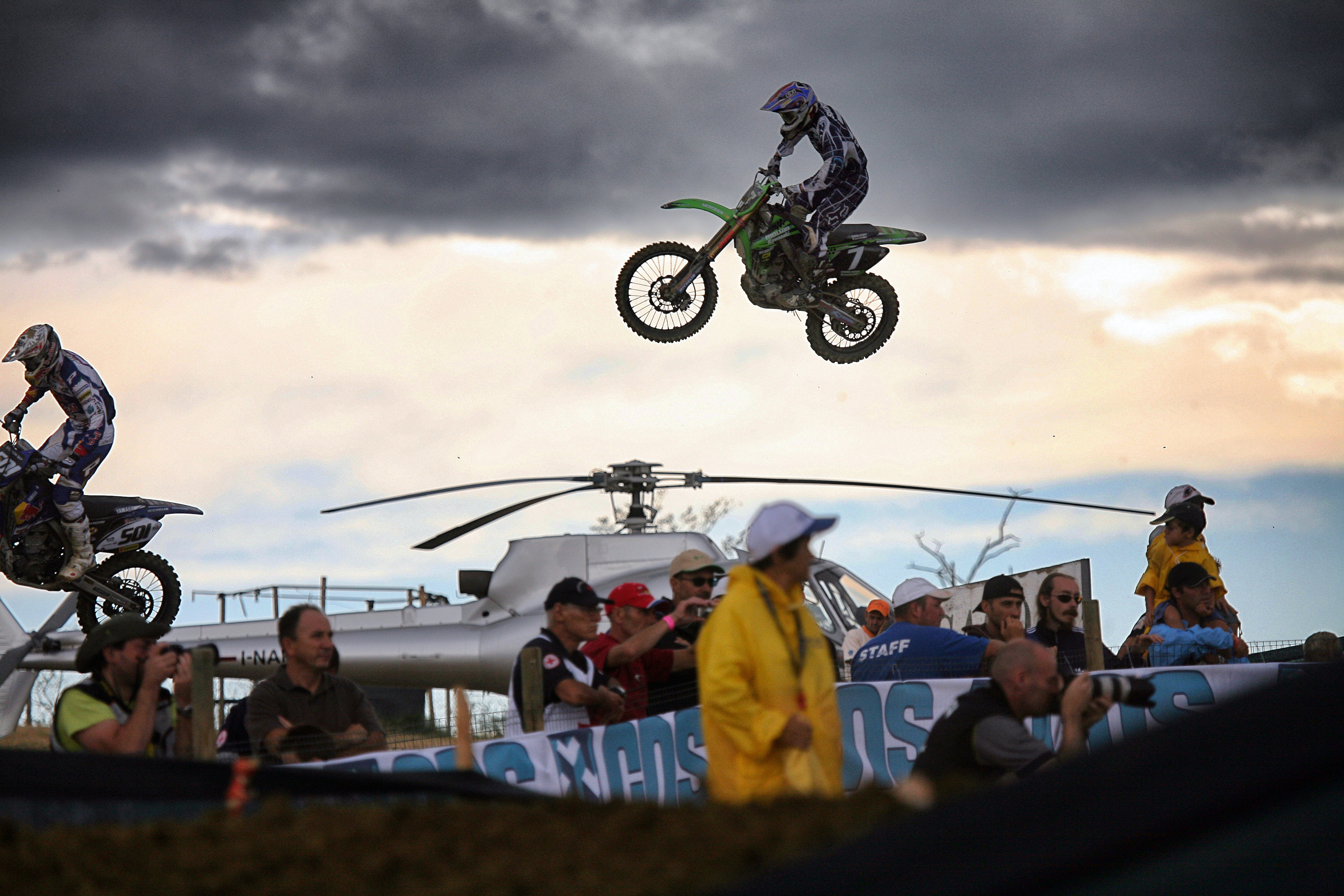 man riding motocross dirt bike over crown of people during daytime