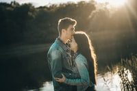 man kissing woman's forehead in front of lake