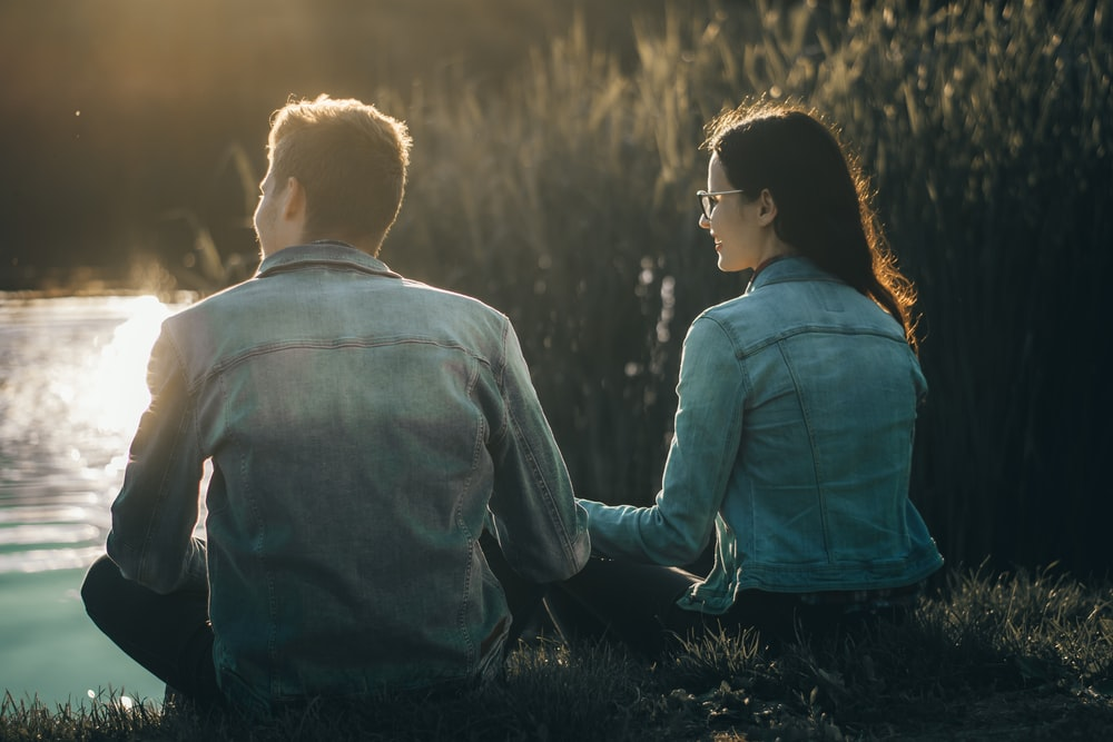 man and woman sitting near body of water