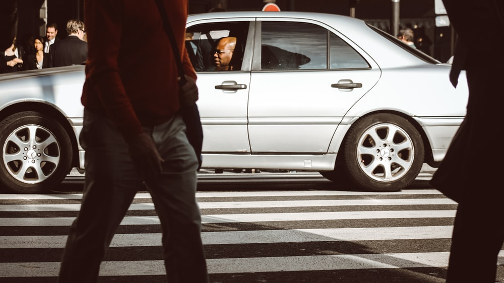 man sitting inside car on street during daytime