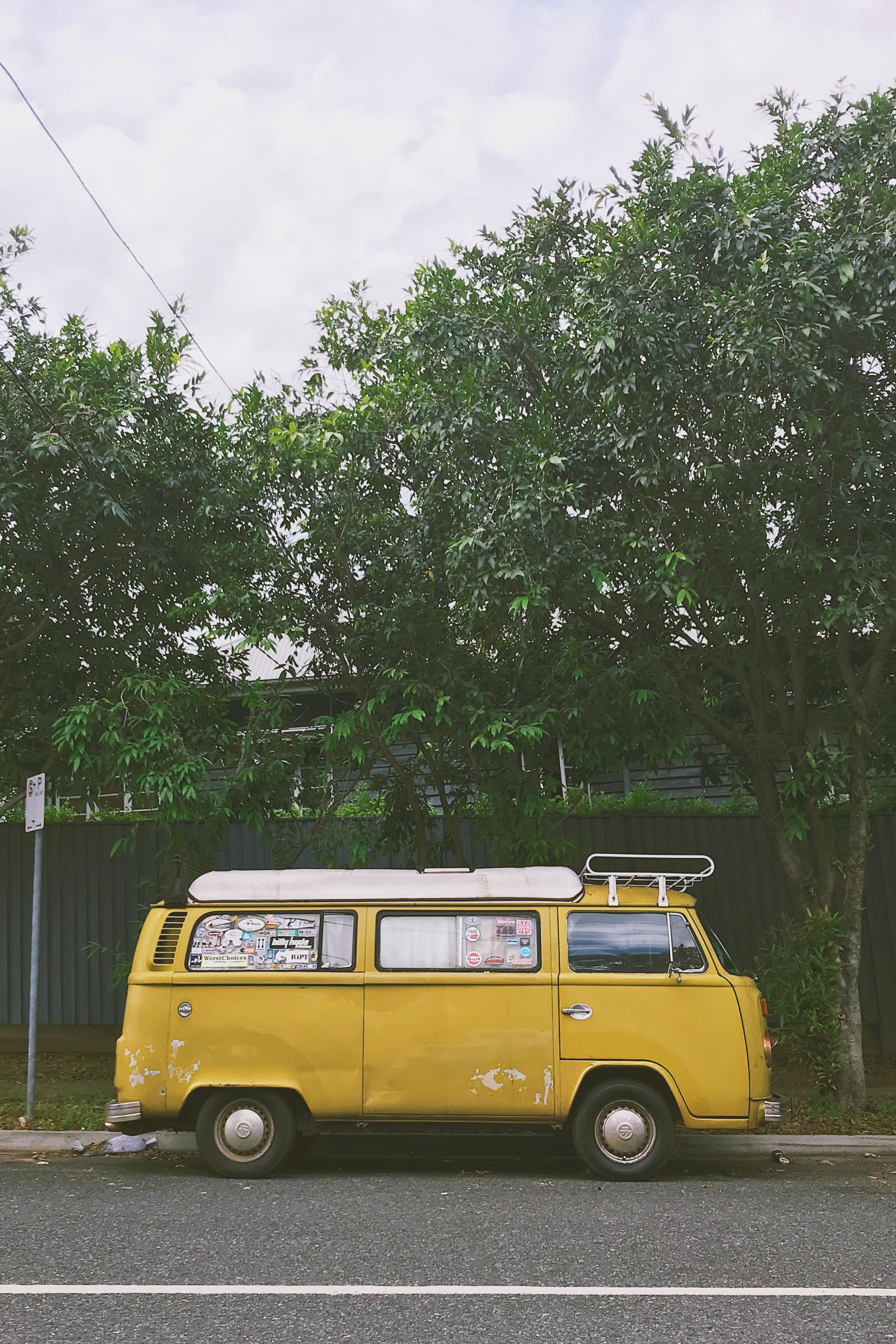 yellow van parked near trees