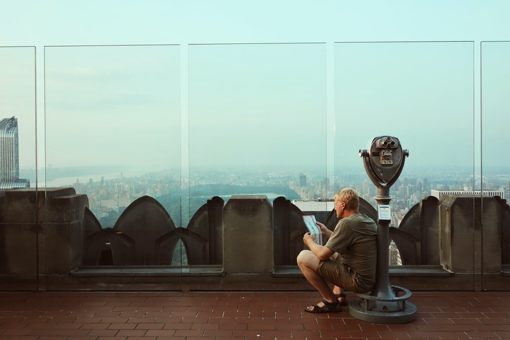 man sitting alone while reading paper on coin-operated telescope